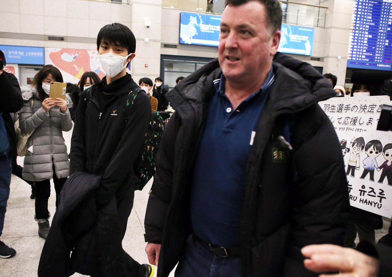 韓国の仁川国際空港に到着した羽生(左)は横断幕を持つファンの前を通り過ぎる(撮影・浅見桂子)