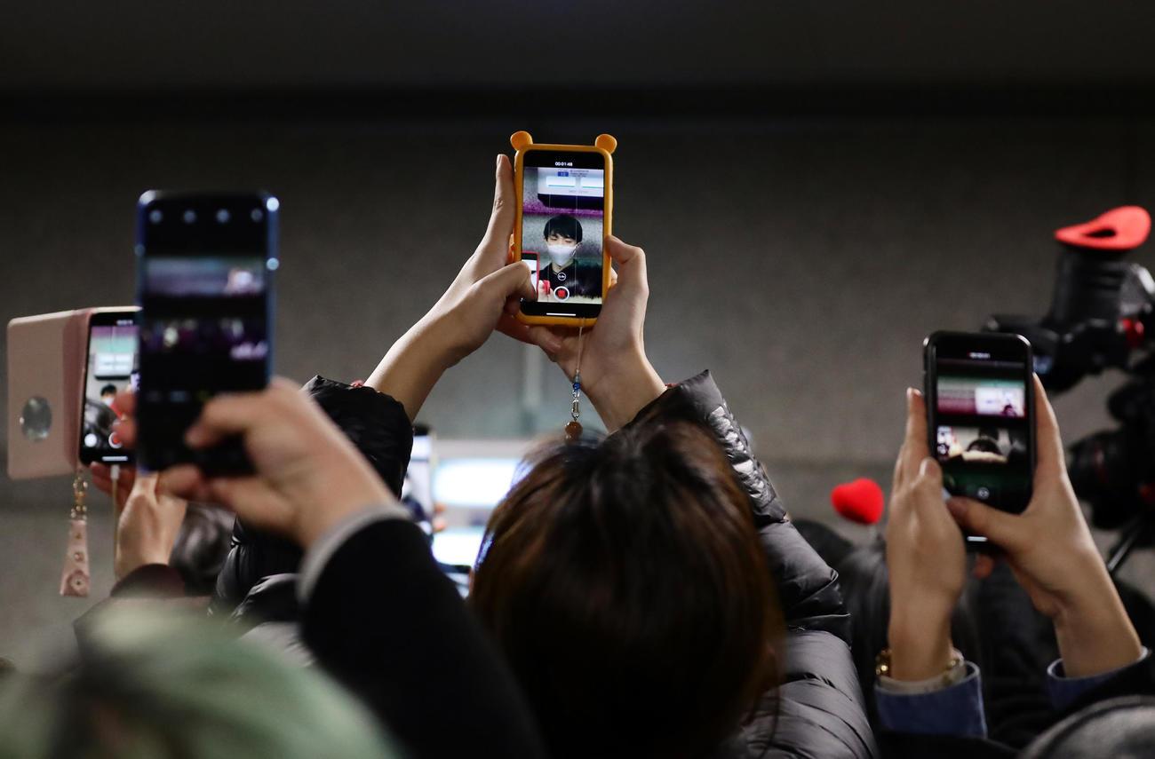 韓国の仁川国際空港に到着した羽生は、通路で報道陣の質問に答えるも集まったファンに囲まれスマートフォンの写真攻めに合う(撮影・浅見桂子)