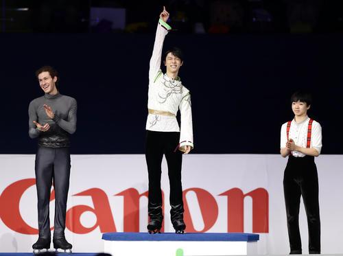 初優勝を決めた羽生(中央)は、表彰台に登ると指を突き上げ笑顔を見せる。左はジェイソン・ブラウン。右は鍵山(撮影・浅見桂子)