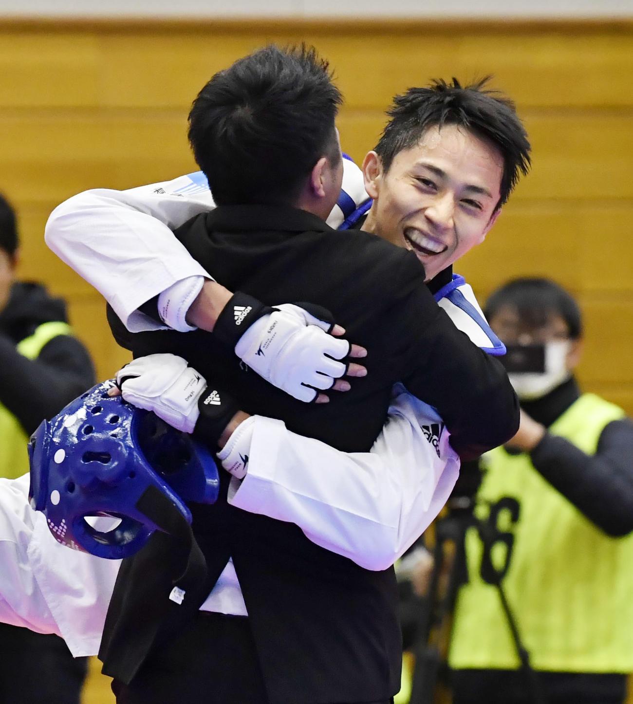 男子58キロ級で東京五輪日本代表に決まり、笑顔で関係者と抱き合う鈴木セルヒオ(共同)