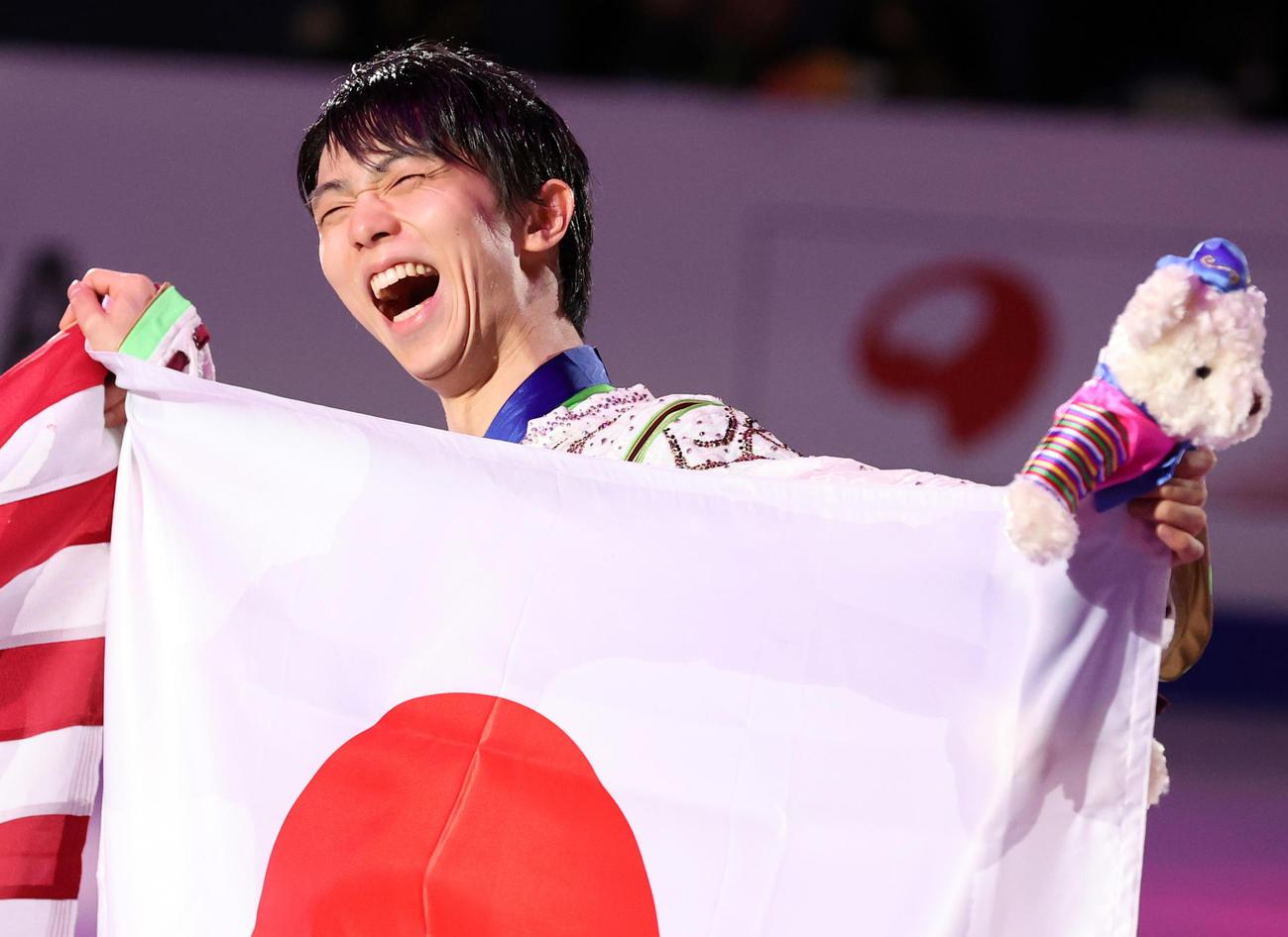 初優勝の羽生は、日の丸を手に笑顔(撮影・浅見桂子)