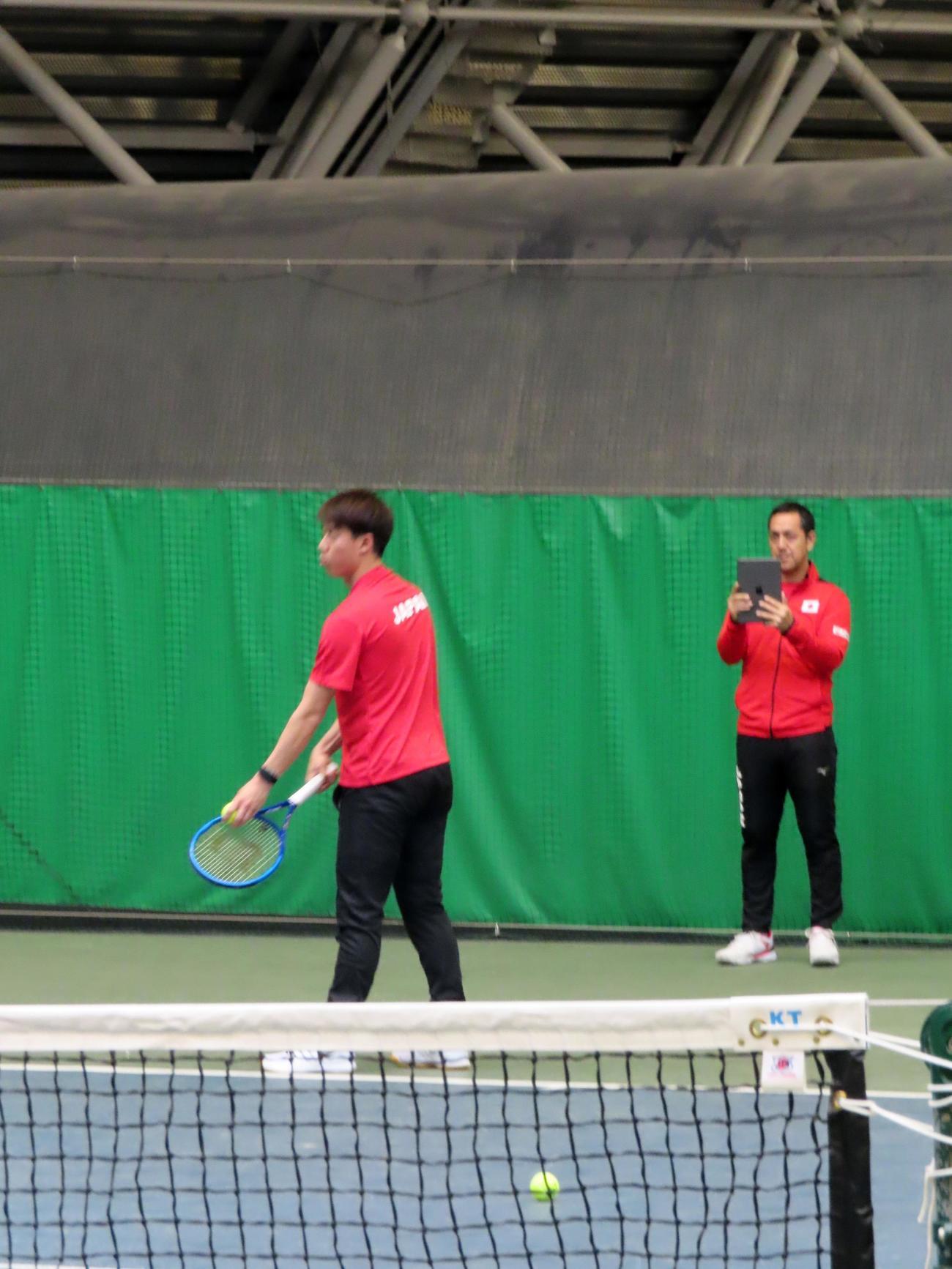 サーブの練習をする錦織を高田コーチが撮影