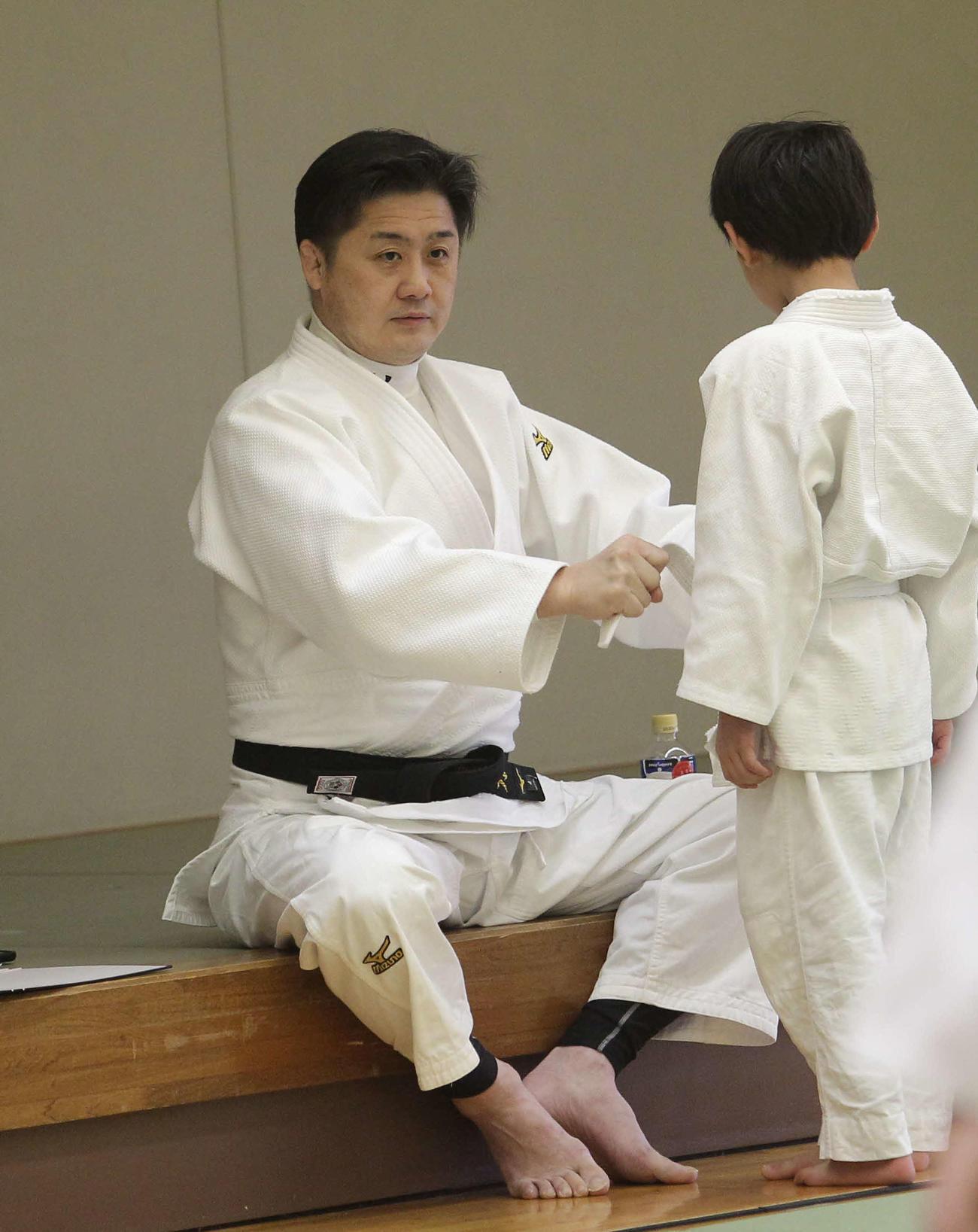 練習を見つめながら塾生の帯を締める星野監督