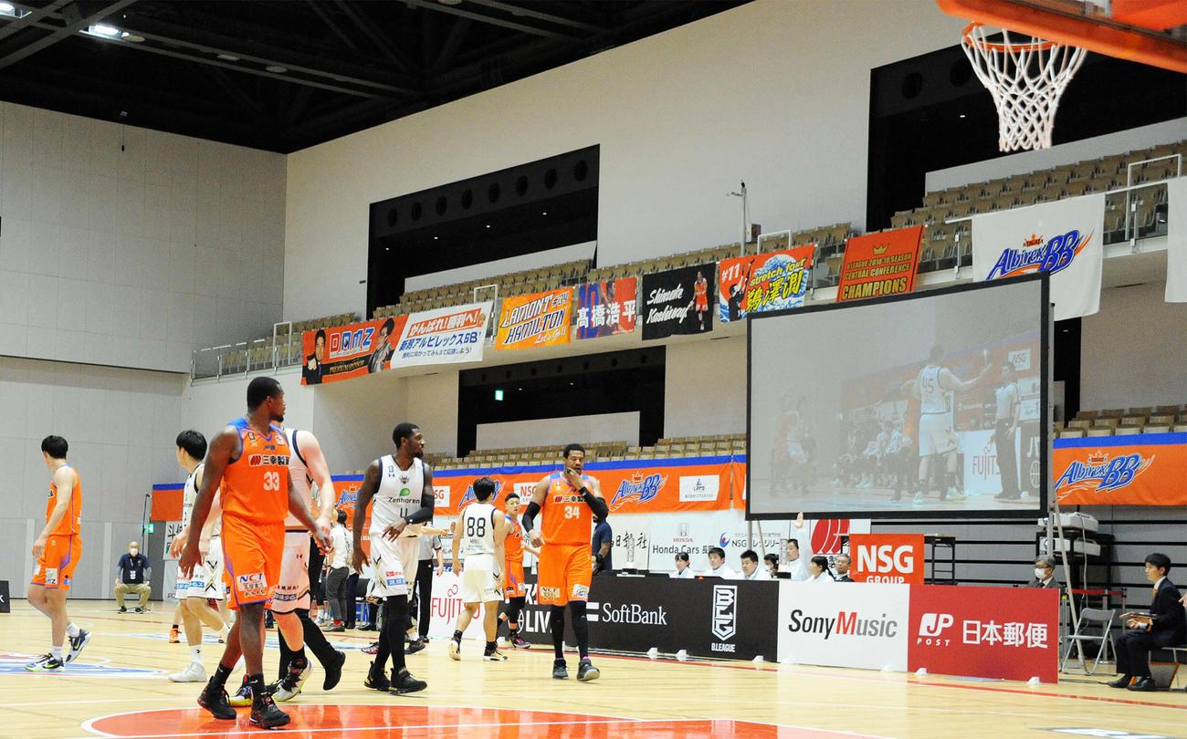 無人のスタンドに囲まれながらプレーする新潟と琉球の選手たち(撮影・斎藤慎一郎)