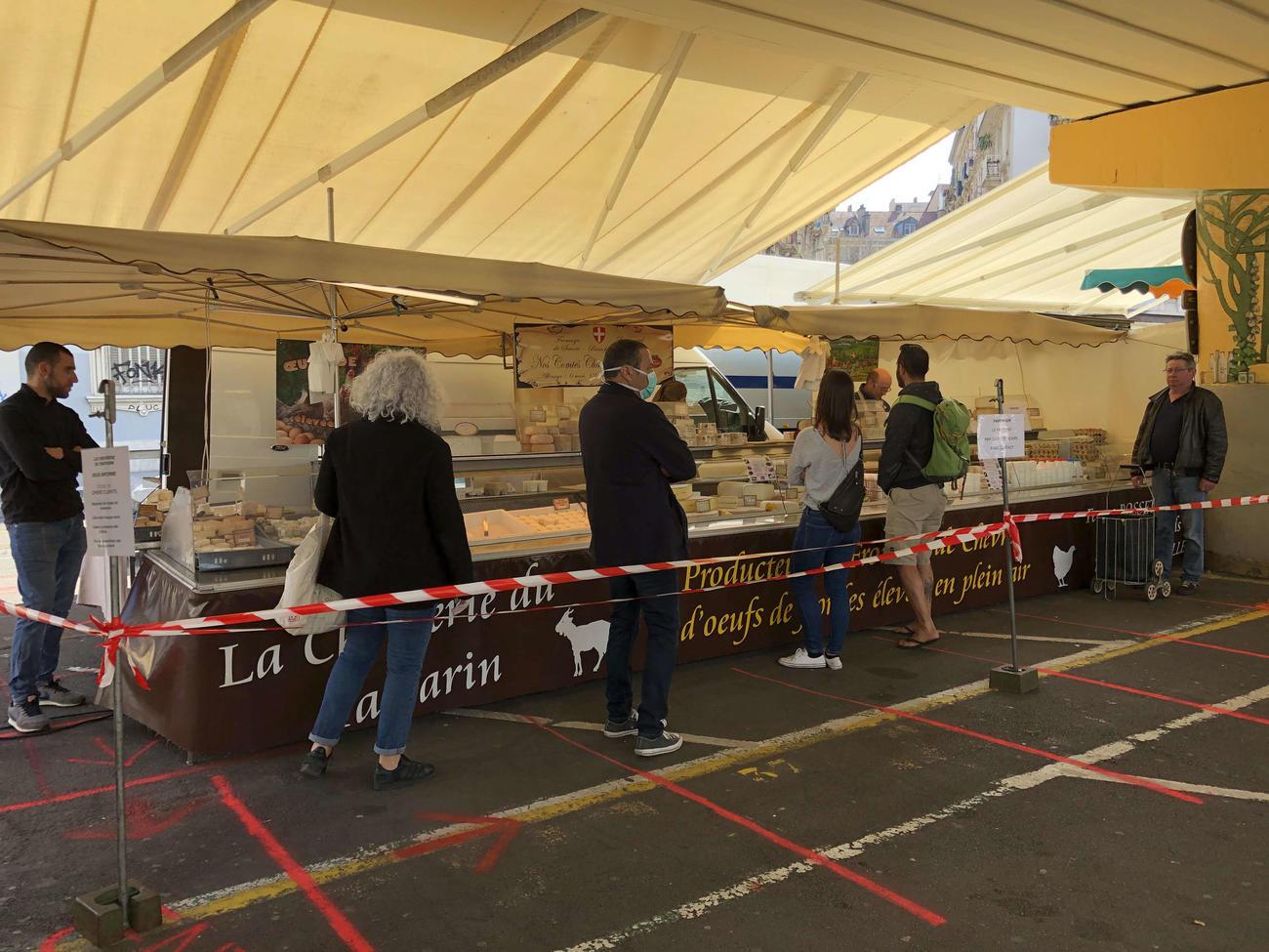マルシェのチーズ店の地面には1メートル間隔のラインやテープで仕切られている
