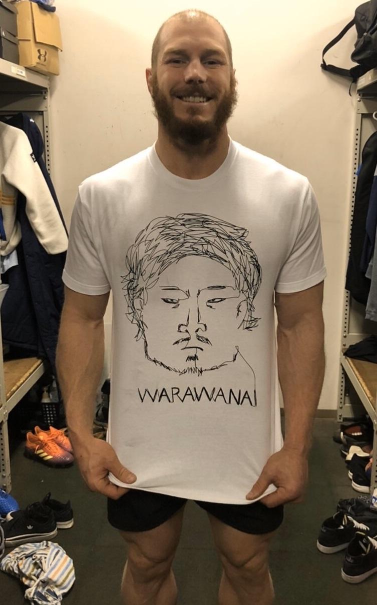 稲垣啓太の似顔絵が描かれた「笑わないTシャツ」を着るデービッド・ポーコック
