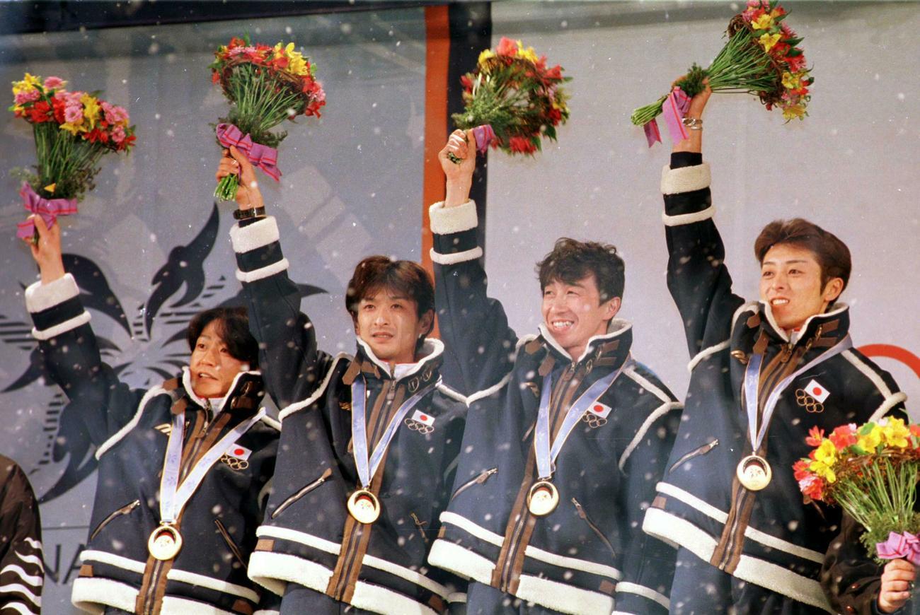 長野五輪ジャンプ団体で金メダルを獲得しフラワーセレモニーで笑顔の(左から)岡部孝信、斎藤浩哉、原田雅彦、船木和喜(1998年2月17日撮影)