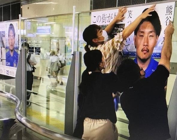 JR熊谷駅に増刷した稲垣啓太のポスターを貼るスタッフら(熊谷商工会議所提供)