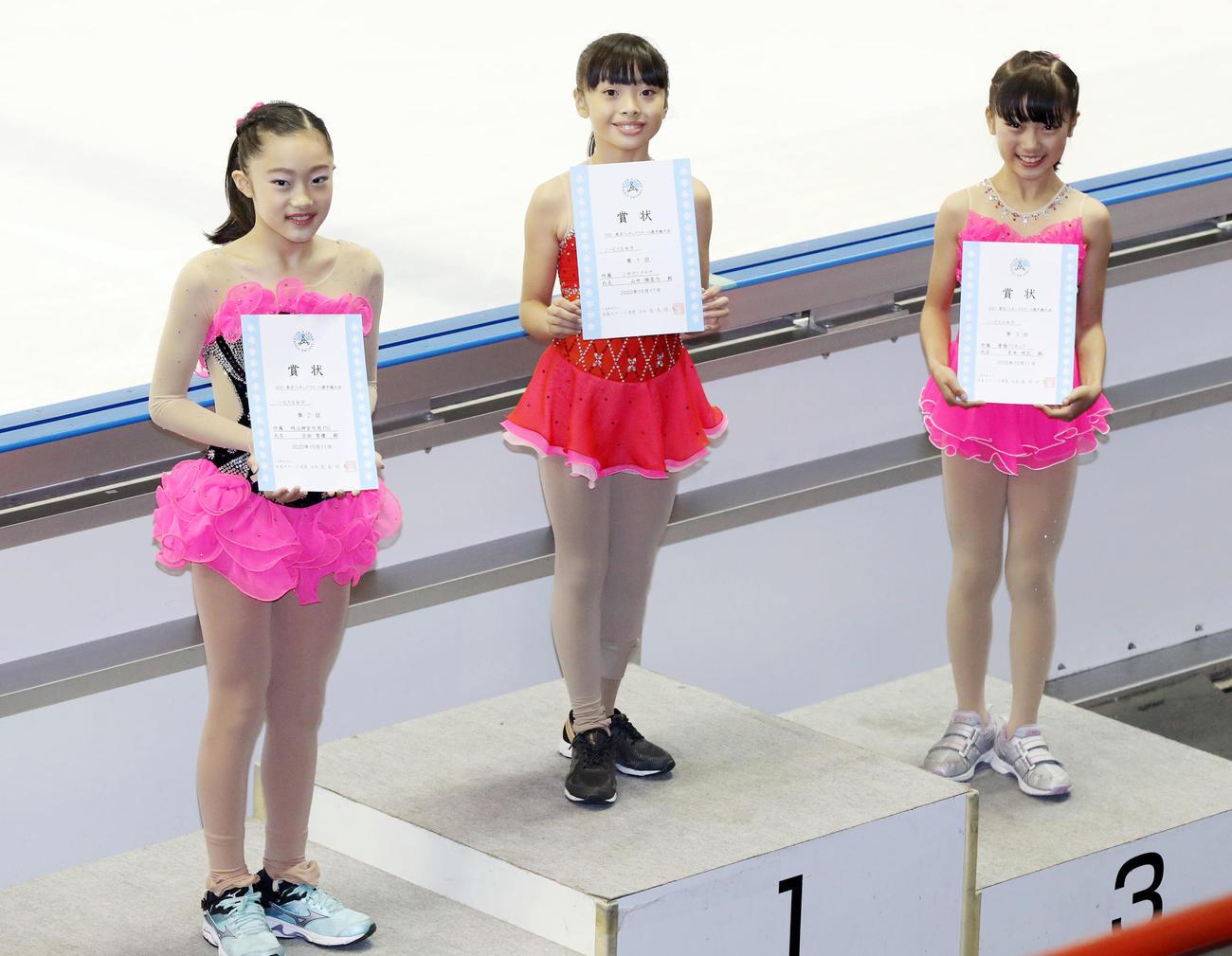 ノービスB女子の表彰式で笑顔を見せる優勝した山中(中央)。左は2位の吉田、右は3位の宮本(撮影・狩俣裕三)