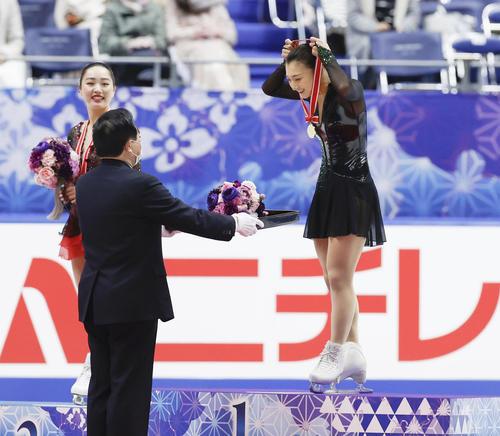感染症予防のため、自らメダルを手に取り、首にかける優勝した坂本花織(右)(代表撮影)