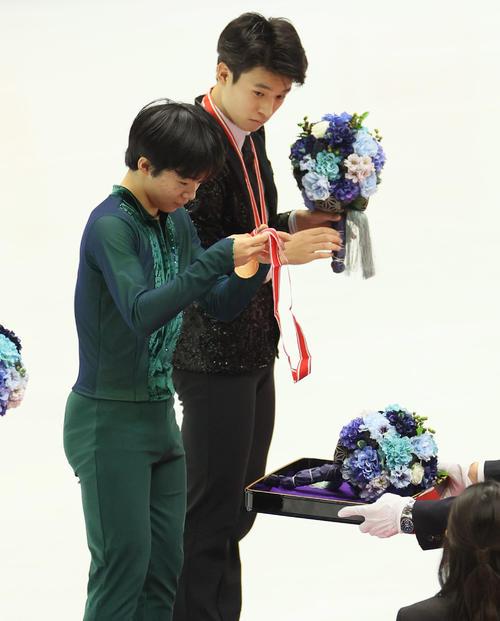 表彰式でメダルを見つめる、優勝した鍵山優真(手前)。奥は3位の本田ルーカス剛史(代表撮影)