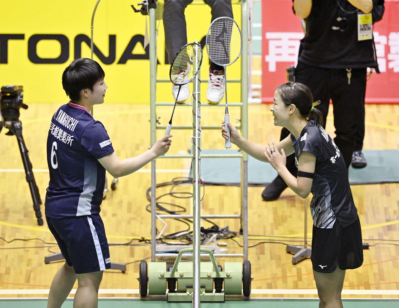 女子シングルスで優勝し、山口(左)とネット越しにラケットでタッチする奥原(代表撮影)