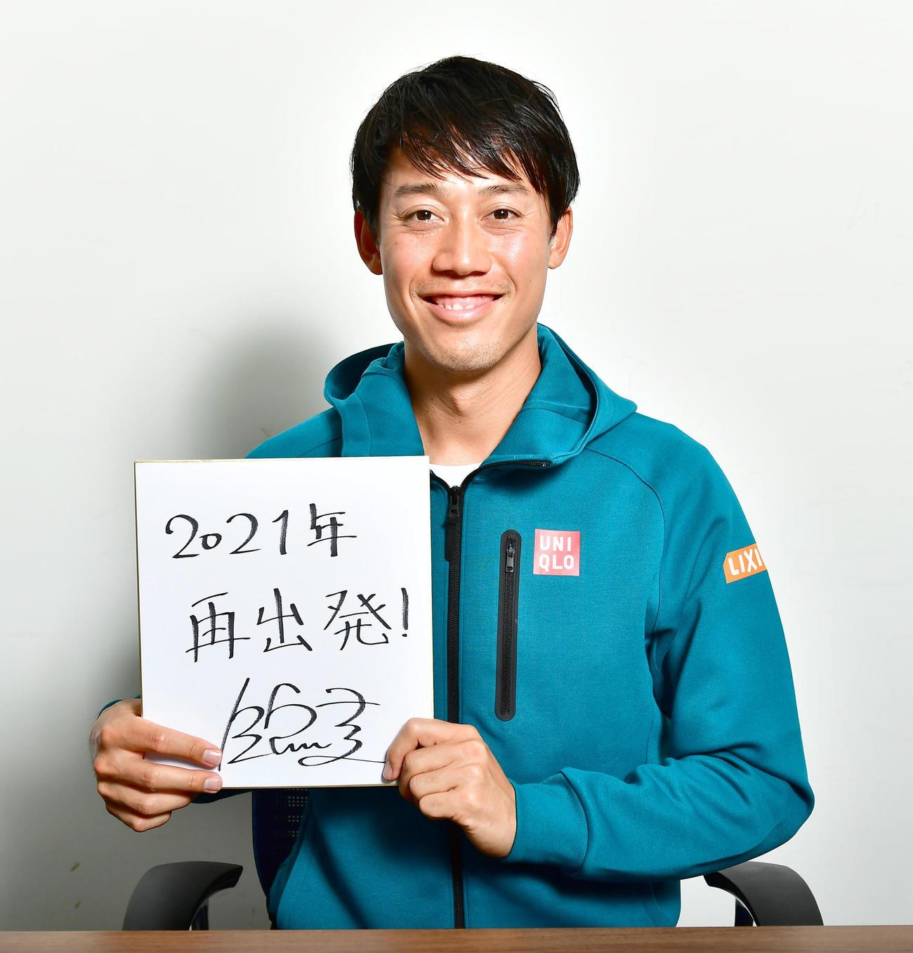 新年の目標を「再出発!」と記した色紙を手に笑顔を見せる錦織(撮影・小沢裕)