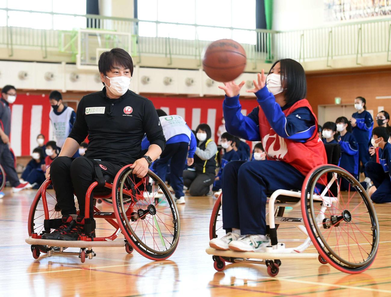 中学生が体験する様子を見守る根木氏(左)(撮影・相沢孔志)