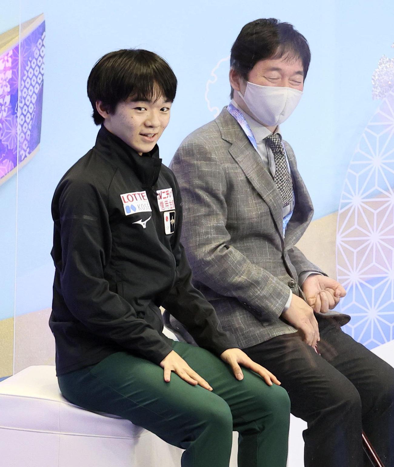 20年11月、NHK杯で男子フリーの演技を終え、キスアンドクライで笑顔の鍵山。右は父の正和コーチ(代表撮影)