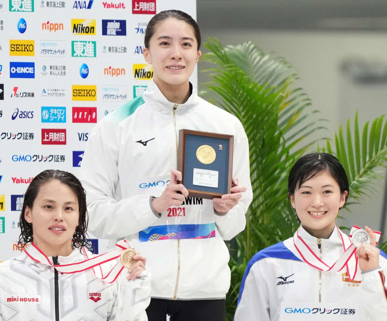 女子400メートル個人メドレーで東京五輪代表内定を決めた優勝の大橋(中央)と2位の谷川(右)は表彰で笑顔。左は3位の清水(撮影・鈴木みどり)
