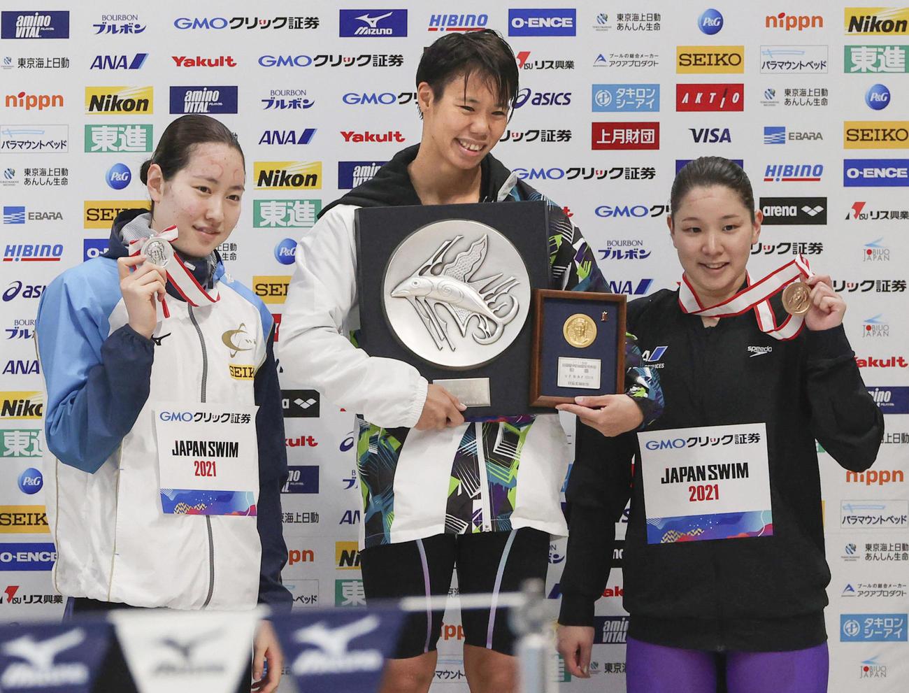 女子100メートル背泳ぎで優勝した小西(中央)。左は2位の酒井、右は3位の赤瀬(代表撮影)