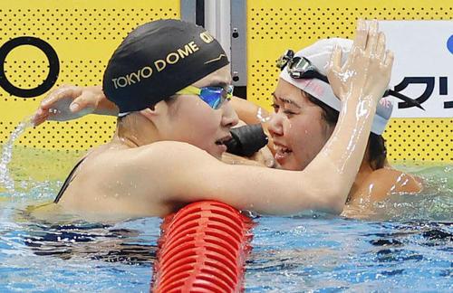 女子200メートルバタフライ決勝のレースを終え、健闘をたたえ合う優勝した長谷川(右)と2位の牧野(代表撮影)