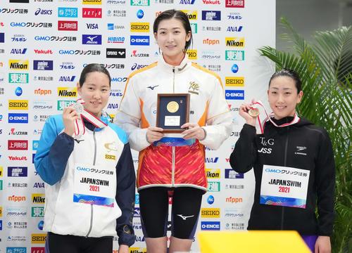 女子100メートル自由形の表彰台で笑顔を見せる優勝の池江(中央)。左は2位の酒井、右が3位の五十嵐(撮影・鈴木みどり)