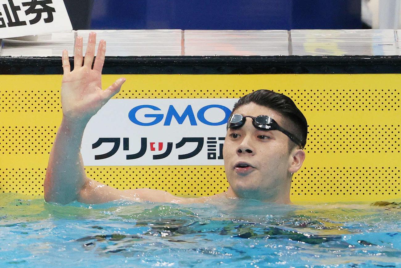 男子100メートルバタフライ決勝で派遣標準記録を突破して優勝し、手を振る水沼(代表撮影)
