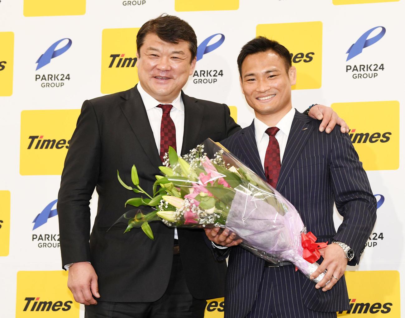 花束を手に笑顔を見せる海老沼匡(右)。左は吉田総監督(撮影・横山健太)