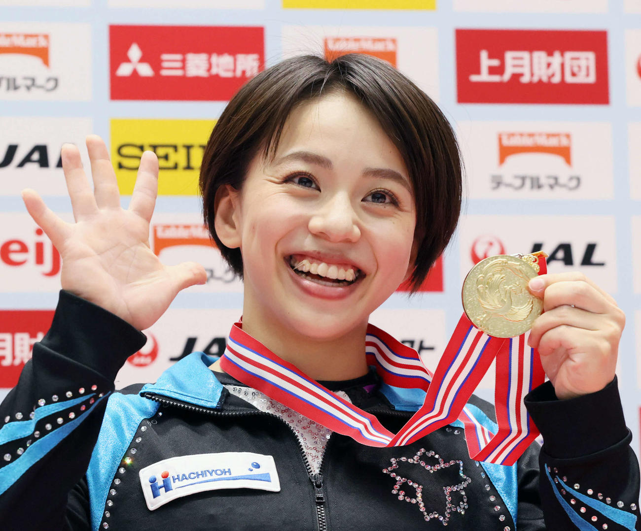 女子個人総合で5回目の優勝を果たし、「5」を手で表す笑顔の村上茉愛(代表撮影)