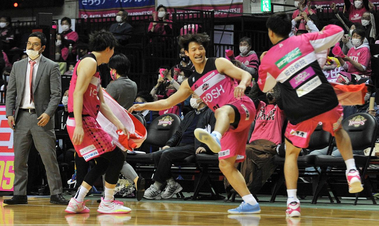 秋田対新潟 前半終了間際、秋田PG長谷川(中央)が47点目のシュートを決め、ベンチでヒップタッチする。左端は前田HC