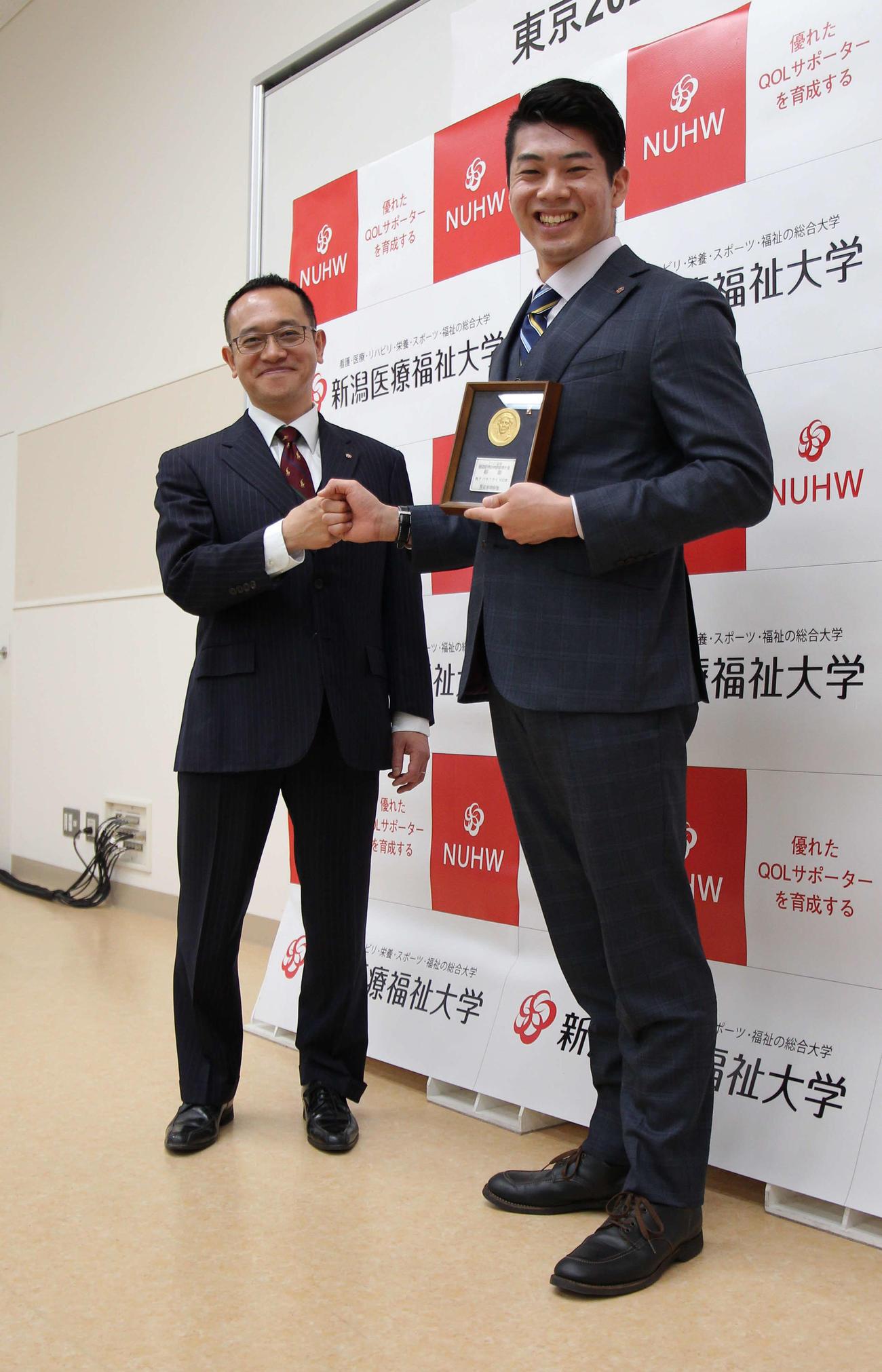 日本代表コーチの下山監督(左)と笑顔でグータッチする水沼
