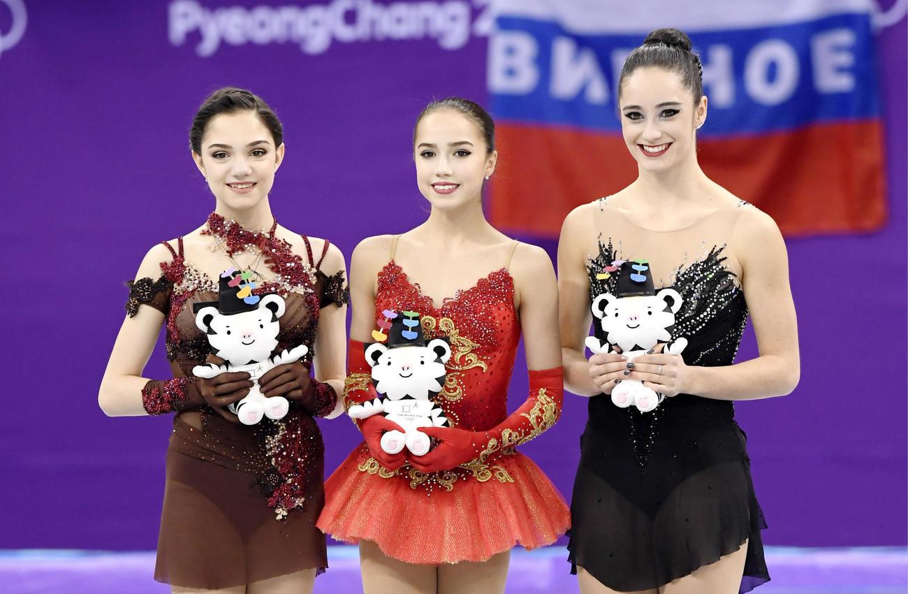 18年2月、平昌五輪フィギュアスケート女子表彰式で笑顔を見せる優勝したザギトワ(中央)。左は2位のメドベージェワ、右は3位のオズモンド