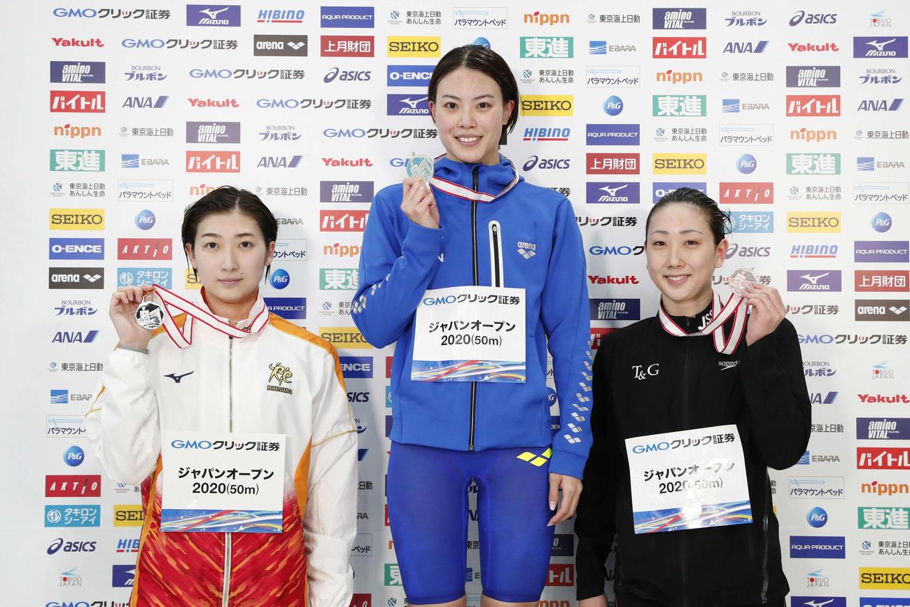 女子50メートル自由形で2位の池江(左)は表彰式でメダルを手にする。中央は優勝の大本、右は3位の五十嵐(日本水泳連盟提供)