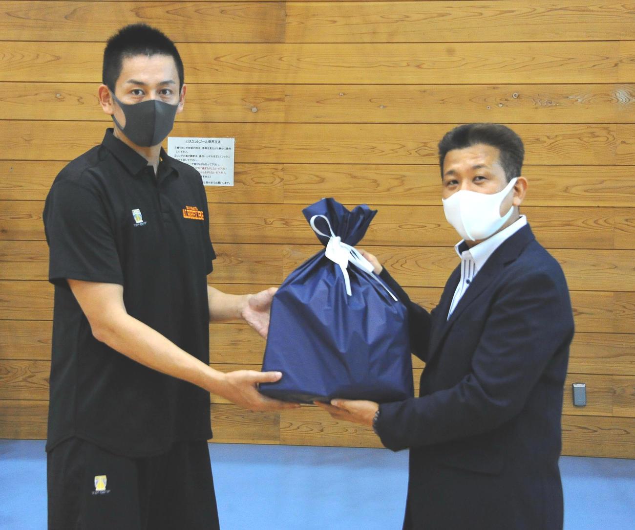 リカバリーウエア贈呈式に出席したB1新潟・池田(左)とベネクス星副社長