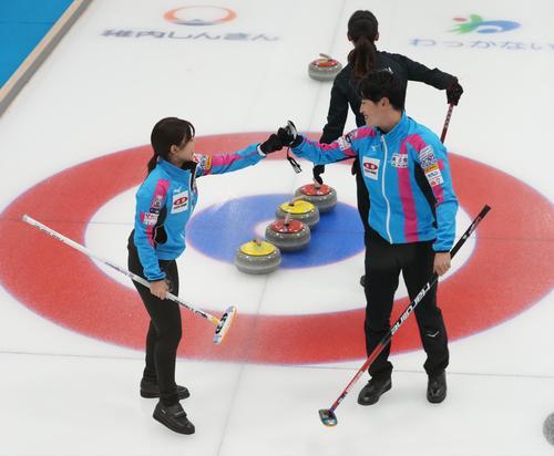 決定戦第2試合の第1エンド、タッチを交わす吉田(手前左)と松村雄(代表取材)