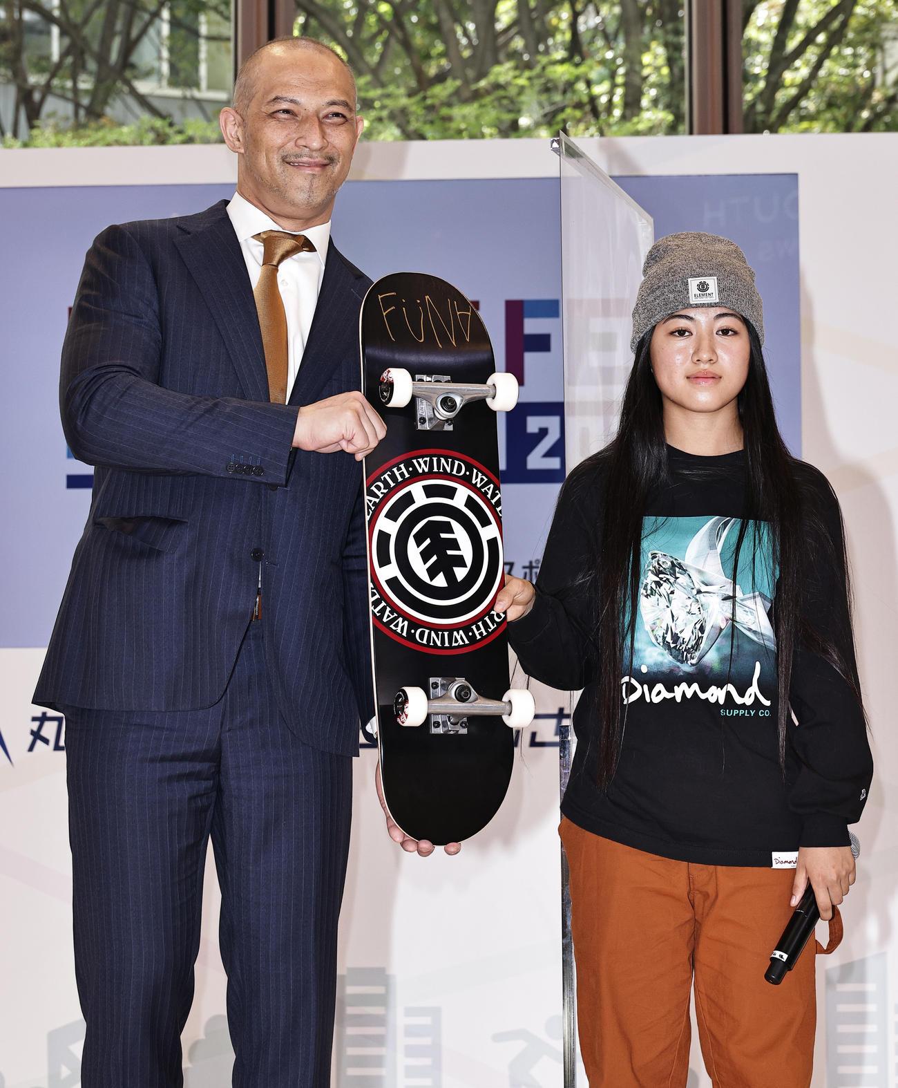 「MARUNOUTI SPORTS FES 2021」で東京五輪スケートボード・ストリート女子銅メダルリストの中山楓奈(右)からスケートボードを贈られた室伏広治スポーツ庁長官(撮影・中島郁夫)
