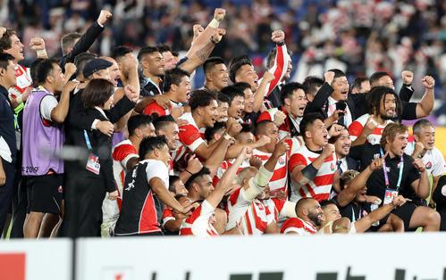 決勝トーナメント進出を決め、記念撮影する日本代表の選手たち(撮影・狩俣裕三)