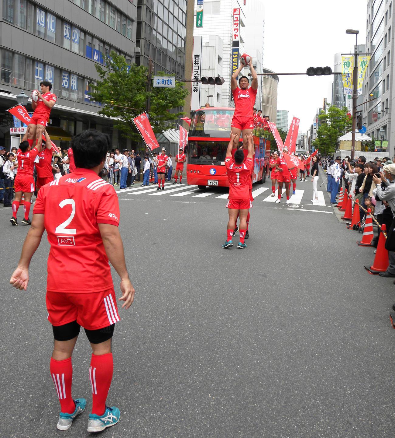 神戸まつりのパレード中にラインアウトを披露する神戸製鋼の選手たち(撮影・松本航)