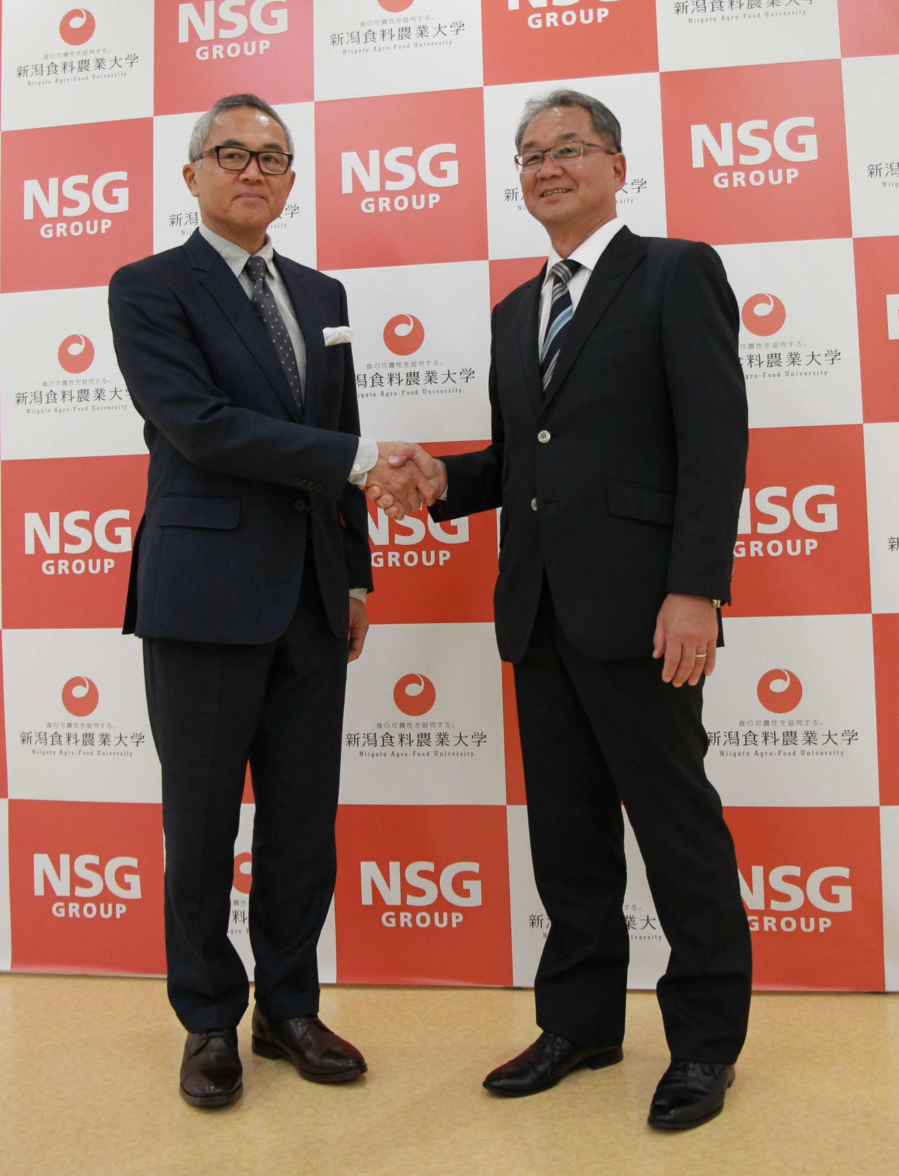 新潟食農大・中井副学長(左)と笑顔で握手を交わす谷崎監督